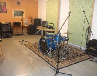 Photograph of Groovehaven's music room. Blue Pearl Drums sit in the foreground.